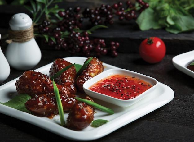 Nuggets de poulet au teriyaki sauca et piment au chili dans une assiette blanche Photo gratuit