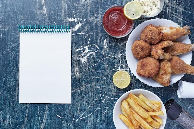 Nuggets De Poulet Avec Pommes De Terre Et Sauces Avec Un Cahier De Côté. Photo gratuit