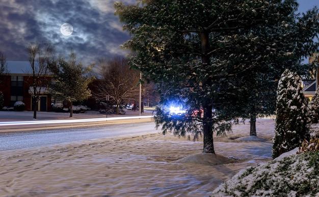 Nuit de phares de voiture d'hiver sur une route de nuit enneigée Photo Premium