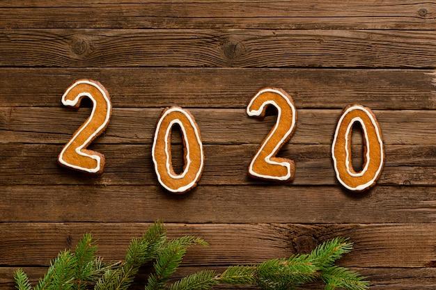 Numéro 2020 fabriqué à partir de biscuits de pain d'épice sur un fond en bois. Photo Premium