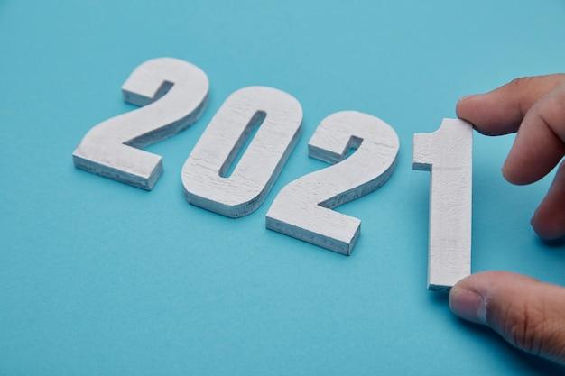 Numéros 2021 Et Main Sur Fond Bleu Pastel Pour Le Nouvel An Photo Premium
