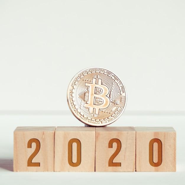 Numéros sur des cubes en bois sur un fond blanc à côté d'une pièce de monnaie bitcoin. Photo Premium