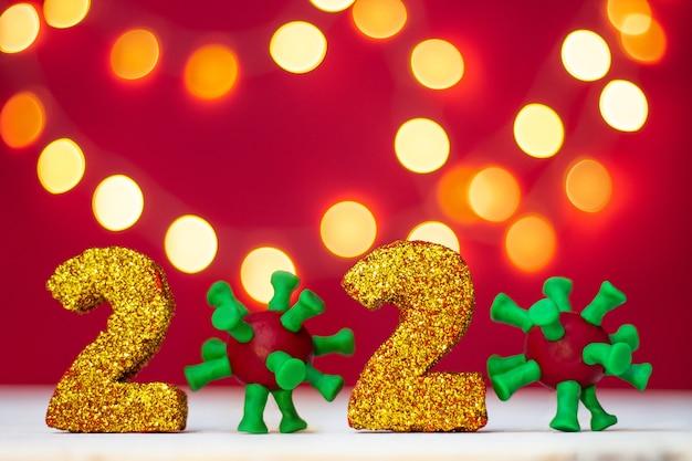 Numéros Scintillants Dorés 2020 Avec Virus Covid-19 Avec Bokeh Sur Fond Rouge. Copiez L'espace. Photo Premium