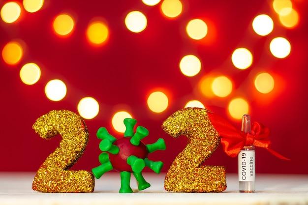 Numéros Scintillants Dorés 2021 Avec Virus Covid-19 Et Ampoule De Vaccin Avec Bokeh Sur Fond Rouge. Copiez L'espace. Photo Premium