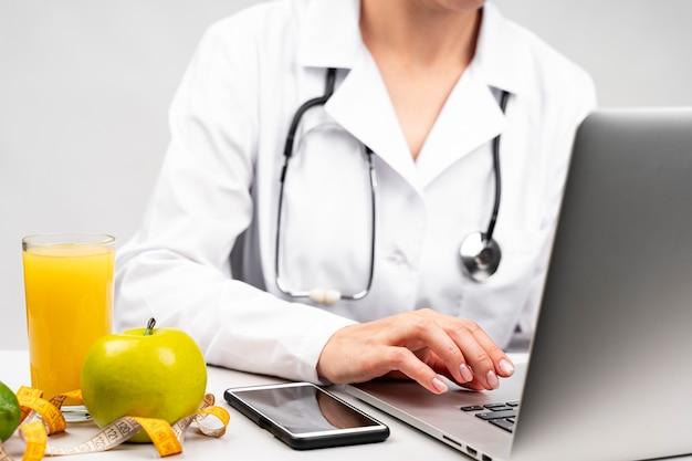 Nutritionniste à L'aide De Son Ordinateur Portable Photo gratuit