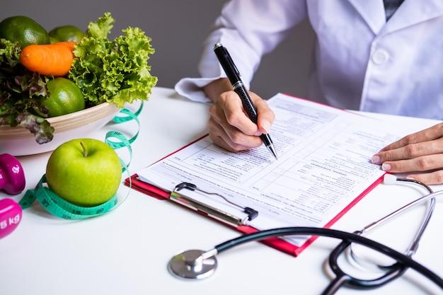 Nutritionniste avec fruits, légumes et ruban à mesurer sains, bonne nutrition et alimentation Photo Premium