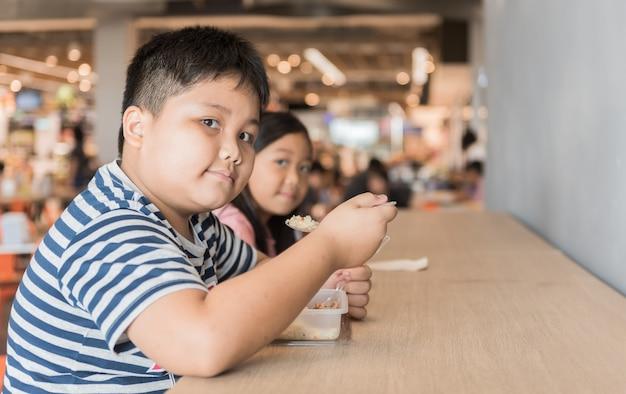 Obèse, frère et soeur, manger, boîte, déjeuner, dans, aire de restauration, concept de fastfood Photo Premium