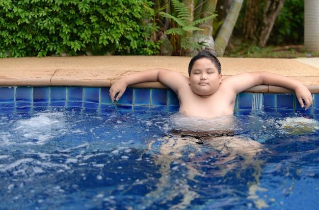 Obèse garçon relaxant en profitant d'un bain à remous Photo Premium