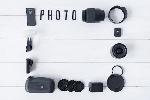 Objectif de la caméra avec accessoires de photographie et texte photo disposé sur une table en bois blanc Photo gratuit
