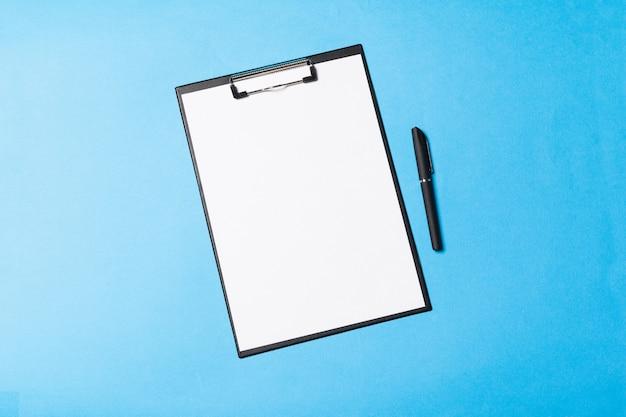 Objets de bureau vides organisés pour la présentation de l'entreprise sur fond de papier bleu Photo Premium