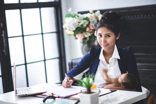 Occupé jeune femme travaillant ou étudier sur un ordinateur portable tout en tenant son bébé dans les bras à la maison Photo Premium