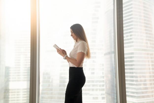 Occupé, sérieux, femme affaires, utilisation, tablette numérique, debout, grande fenêtre Photo gratuit