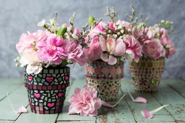 Oeillet en pot de fleur de mosaïque sur le vieux bois Photo Premium