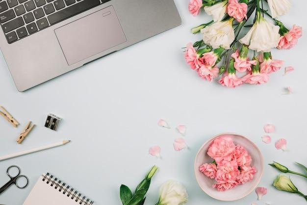 Oeillets et fleurs d'eustoma sur ordinateur portable; crayon; ciseaux; taille-crayon et bloc-notes à spirale sur le bureau bleu Photo gratuit