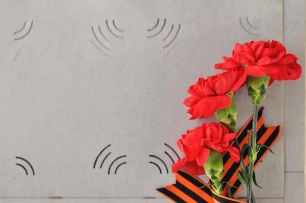 Oeillets rouges et ruban st. george sur le fond d'un vieil album photo. jour de mémoire et de gloire militaire. Photo Premium
