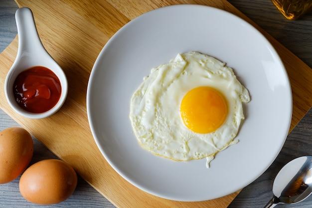 L'œuf Au Plat Est Dans Un Plat Rond Blanc Placé Sur Une Planche à Découper, Vue De Dessus Concept Alimentaire Photo Premium