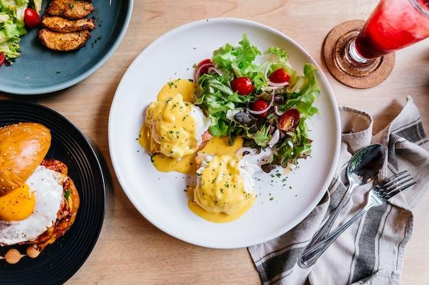 Œuf benedict servi avec salade dans une assiette blanche sur une table en bois pour un délicieux petit déjeuner et Photo Premium