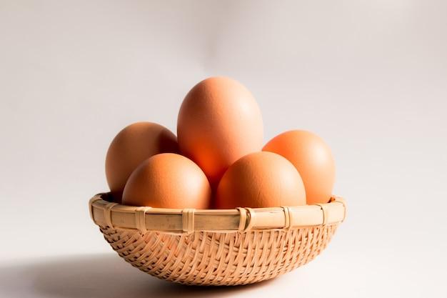 Oeuf dans le panier en osier sur fond blanc, oeufs de canard dans les paniers. Photo Premium