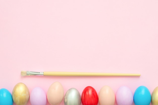 Oeuf de pâques coloré peint en composition de couleurs pastel avec un pinceau Photo gratuit