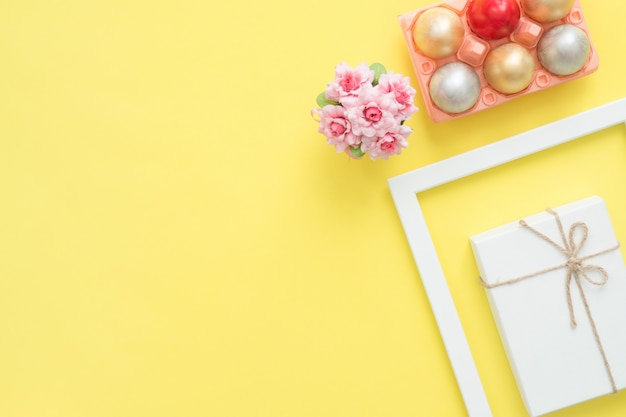 Oeuf de pâques coloré vue de dessus plat lapointe peint en composition de couleurs pastel et fleurs de printemps Photo gratuit