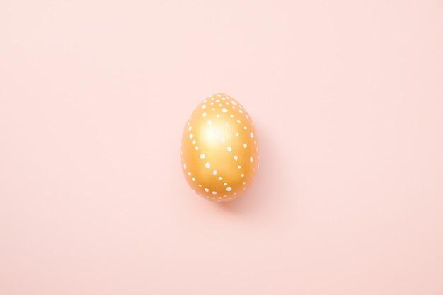 Oeuf de pâques décoré doré sur fond rose pastel. carte de joyeuses pâques Photo Premium