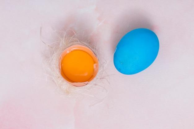 Oeuf de pâques avec oeuf cassé au nid Photo gratuit