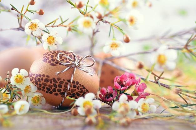 Oeuf de pâques peint sur du bois avec des fleurs blanches et du foin autour Photo Premium