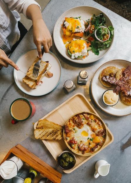 Œufs benedict, pain perdu fourré au bacon croustillant, pomme de terre au fromage avec bacon croustillant et crêpes. Photo Premium