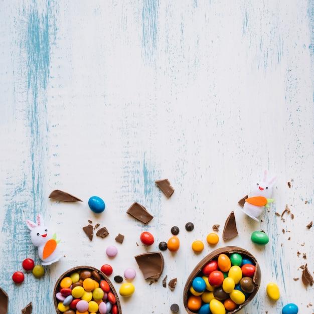 Oeufs cassés avec des bonbons près des lapins Photo gratuit