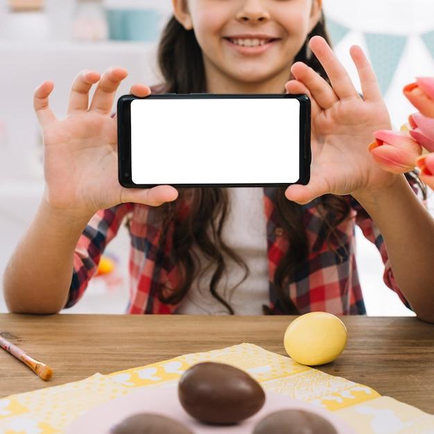 Œufs en chocolat devant une fille montrant un écran blanc sur un téléphone portable Photo gratuit
