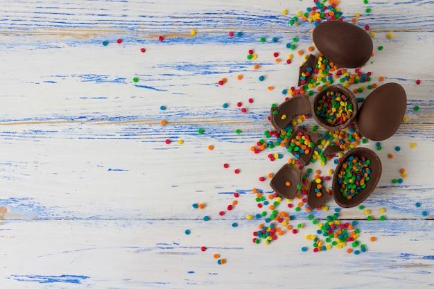Oeufs En Chocolat De Pâques, Bonbons Multicolores Sur La Surface En Bois Blanc. Concept De Pâques. Mise à Plat, Vue De Dessus Photo Premium