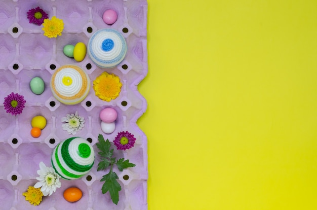 Des oeufs colorés décorent avec de la laine à tricoter pour le jour de pâques et le festival placés dans un plateau à oeufs pourpre. Photo Premium