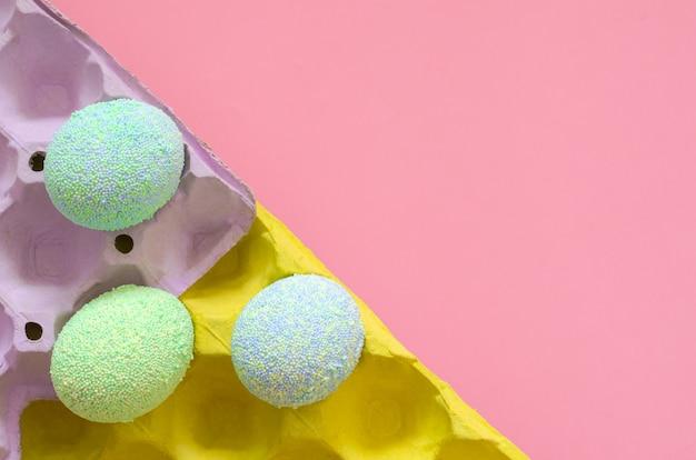 Oeufs colorés pour le jour de pâques et le festival mis dans un plateau d'oeufs violet et jaune avec un fond rose pastel. Photo Premium