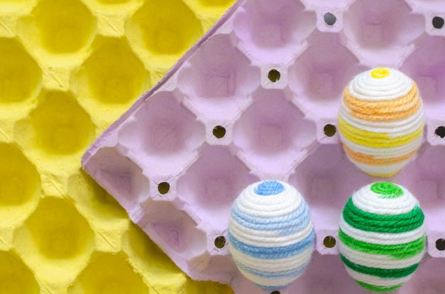 Des oeufs colorés pour le jour de pâques et le festival sont placés dans un plateau à oeufs violet et jaune. Photo Premium