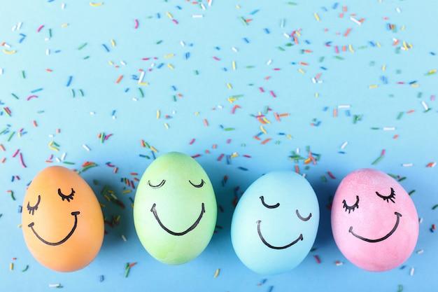 Oeufs colorés avec des sourires peints. conception de carte de voeux joyeux pâques concept. Photo Premium