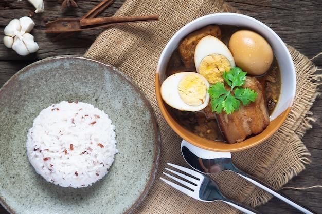 Œufs Cuits Et Porc Ou œufs Et Porc En Sauce Brune Dans Un Bol Avec Du Riz Sur Une Table En Bois Photo Premium