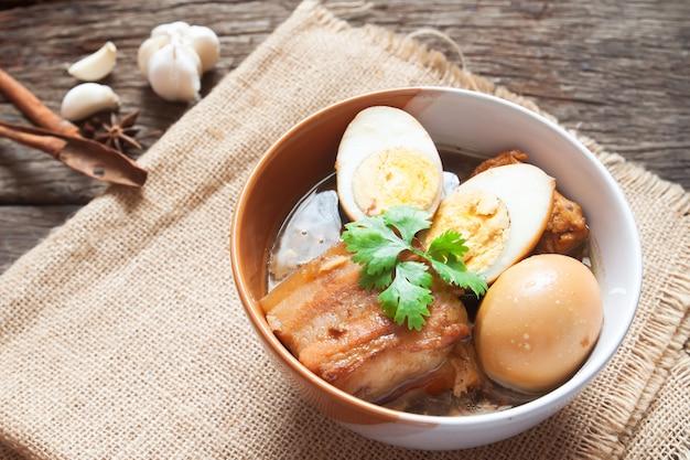 Œufs Cuits Et Porc Ou œufs Et Porc En Sauce Brune Dans Un Bol Avec Des épices Sur Une Table En Bois Photo Premium
