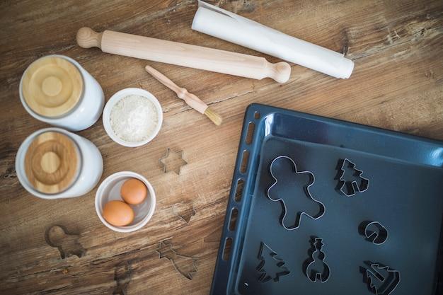 Œufs, farine, rouleau à pâtisserie et moules à biscuits à la lèchefrite Photo gratuit