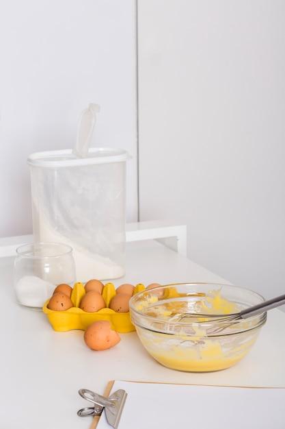 Oeufs fouettés; carton d'oeufs; farine; sel et papier sur presse-papiers sur table Photo gratuit