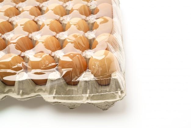 Les oeufs frais dans le paquet sur fond blanc. Photo gratuit