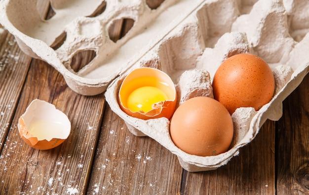 Des œufs frais, dont l'un était cassé, sur une table en bois. Photo Premium