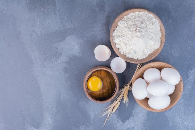 Des œufs Et Un Jaune Jaune Dans Une Tasse En Bois. Photo gratuit