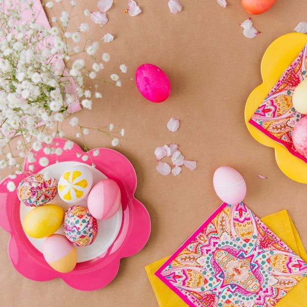 Oeufs de pâques sur une assiette près des serviettes et des fleurs Photo gratuit