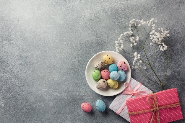 Oeufs de pâques avec un cadeau sur la table en bois. carte de voeux. vue de dessus avec un espace pour vos salutations. Photo Premium