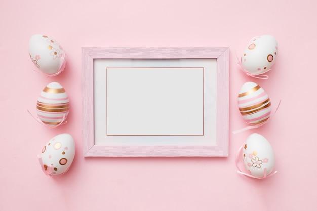 Oeufs De Pâques Et Cadre Photo Blanc Sur Rose Photo Premium