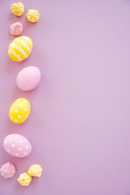 Oeufs de pâques colorés avec des bonbons sur la table pourpre Photo gratuit