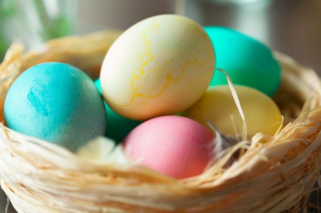 Oeufs de pâques colorés dans un nid de paille Photo Premium