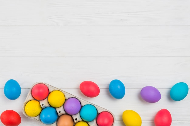 Oeufs de pâques colorés dans le support sur la table lumineuse Photo gratuit