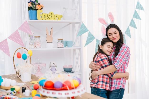 Oeufs de pâques colorés devant la mère et la fille s'embrassant Photo gratuit