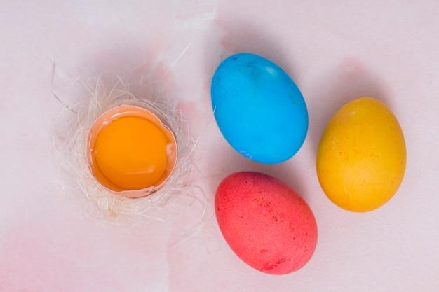 Oeufs de pâques colorés avec oeuf cassé dans le nid Photo gratuit